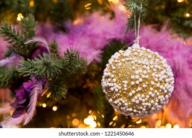 Golden christmas ball with white dots in front of purple and pink christmas decoration