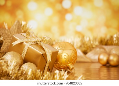 Golden Christmas baubles and a gift in front of defocused golden lights.