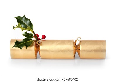 Golden christmas cracker with holly leaf sprig with red berries, over white background with reflection.