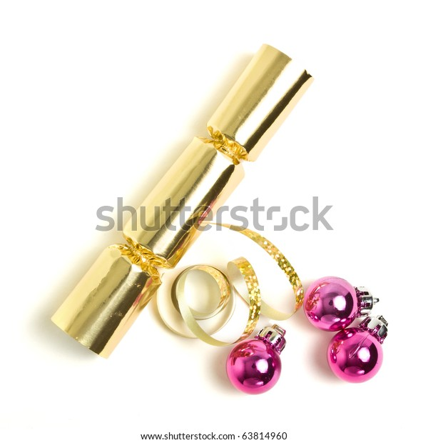 Golden Christmas Cracker with ribbon and pink baubles from overhead.