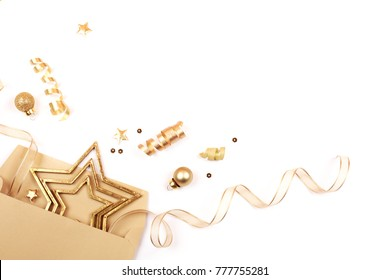 Golden Christmas decorations expands from the gift envelope. Stars, glitters balls and ribbons are isolated on white background. Christmas greeting concept.
