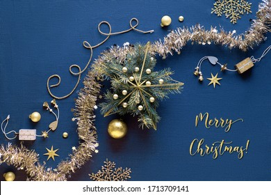 "Golden Christmas decorations, flat lay on blue linen table cloth. Diagonal festive arrangement with gold garland, baubles, geometric Xmas star with fir twigs and trinkets. Text ""Merry Christmas""."
