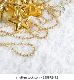 Golden  Christmas decorations on a snow background