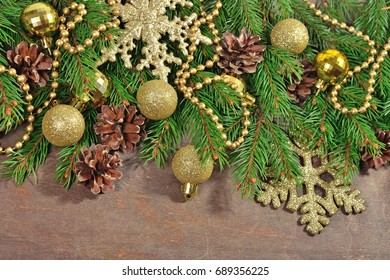 Golden Christmas decorations and spruce branch and cones on a wooden background