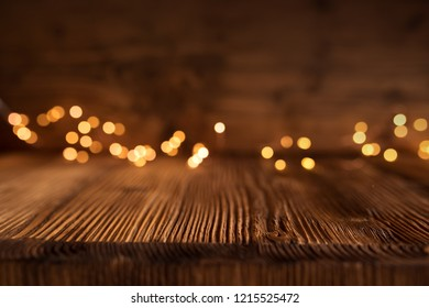 Golden christmas lights on empty wooden table for a decoration