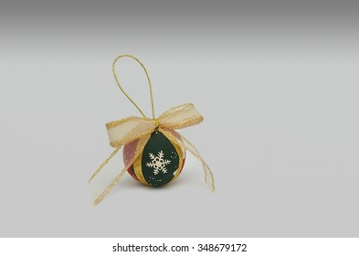 golden Christmas ornament with red and green and snow symbol