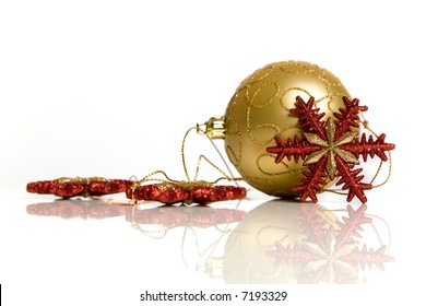 Golden christmas ornament and snowflakes on reflective table