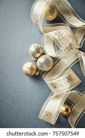 Golden Christmas Ornaments with Satin Ribbon on Gray Background. Christmas background. Top view. Copy space.