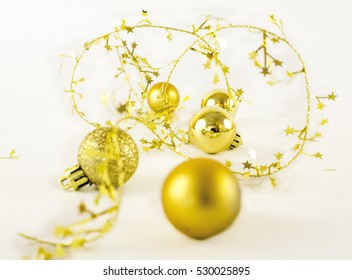 Golden christmas spheres and stars on a white background.