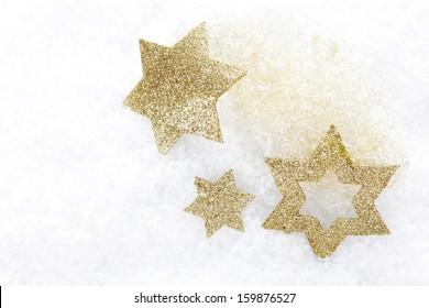 golden christmas stars on artificial snow