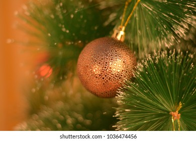 Golden christmas tree toy in greenery.