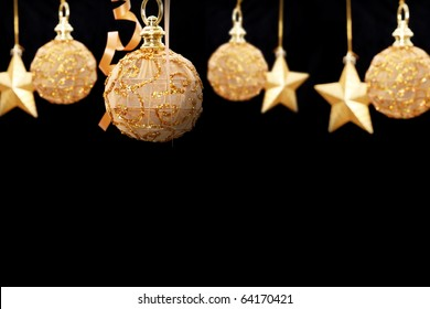 Golden chrsitmas balls on black background, space to insert text or design