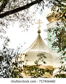 The Golden Church Dome of the Orthodox Church view through trees close up