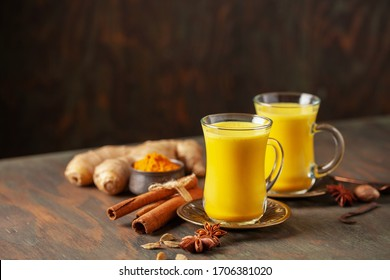 Golden Cinnamon  Turmeric Milk. Trendy hot Healthy drink with turmeric roots and spices. Indian Masala Haldi Doodh. Wooden background