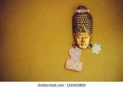 Golden closed-eye mask with flower crown and number one. Yellow, ocre background