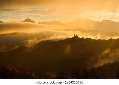 Golden clouds and fog at sunrise in the mountains of Kamnik Savinja Alps in Skofjelosko Hills with St Thomas church silhouette near Ljubljana Slovenia