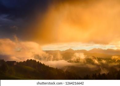 Golden clouds and fog at sunrise in the mountains of Kamnik Savinja Alps in Skofjelosko Hills with St Thomas church near Ljubljana Slovenia