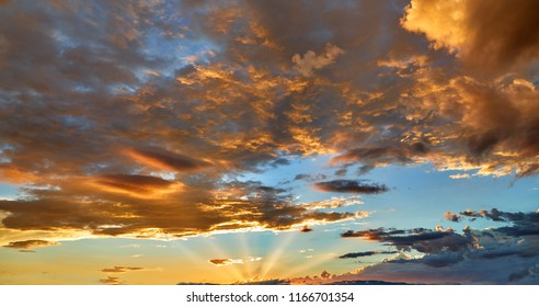 Golden clouds in a sunset sky with the sun rays shining on them
