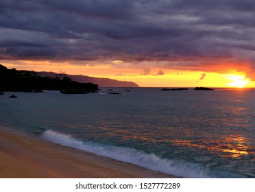 Golden and cloudy sunset at Waimea Bay on the North Shore, Oahu, Hawaii.  Waves lapping on shore with sun reflecting in water and sand.  Famous jumping rock on the far left.