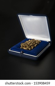 Golden coffee beans symbolizing in a precious box on black background.
