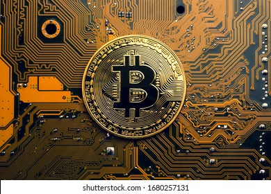 A golden coin with bitcoin symbol on a mainboard. - Shutterstock ID 1680257131
