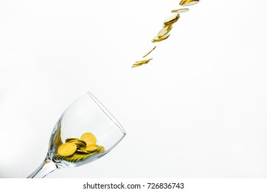 Golden coins splash in a glass of champagne on the wall background with copy space., saving money concept.