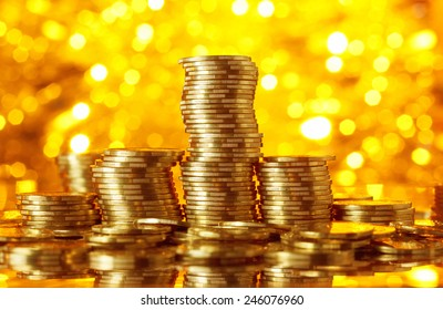 Golden coins stacks on bright light glowing bokeh background, business finance wealth and success concept