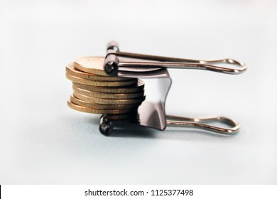 golden coins tightened up in a clamp, financial crisis concept or inflation, austerity, budget control conceptisolated, on white background.