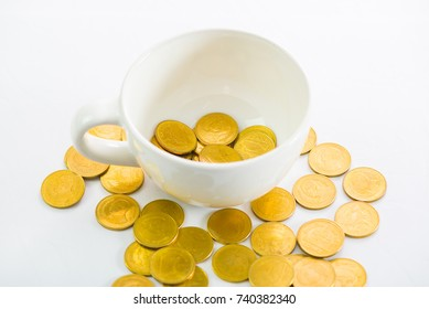 Golden coins in a white cup  of coffee on the white background saving money concept.