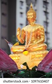 Golden color buddha statue decorated with  flower garland mounted on a wesak procession vehicles parked outside Maha Vihara buddhish temple, Kuala Lumpur Malaysia, on wesak day.