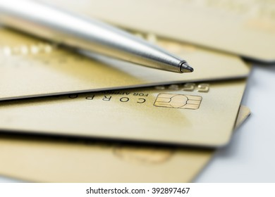 Golden color credit cards with a ballpen