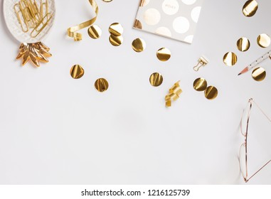 Golden color decor and confetti on the white background, top view
