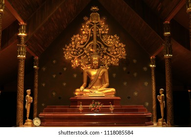 golden color meditating Gautama buddha ststue image with two disciples praying in the front and Bodhi tree in the back. Secred buddhist image in an old wooden temple. peace of mind and soul concepts