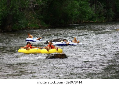 GOLDEN, COLORADO - July 25, 2015 - People inner tubing down Clear Creek to cool off from the summer heat