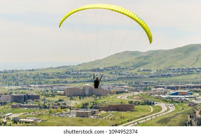 Golden, Colorado, USA - May 9, 2018: A paraglider flying high above Highway 6 near city of Golden, with Jefferson County Government Center building in background below.