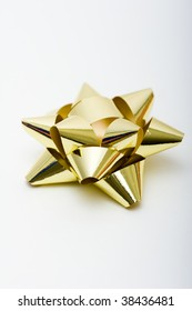 A golden colored gift bow isolated against white