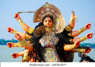 Golden and colorful statue of ten handed goddess Durga being worshiped with flower in Kolkata, India.