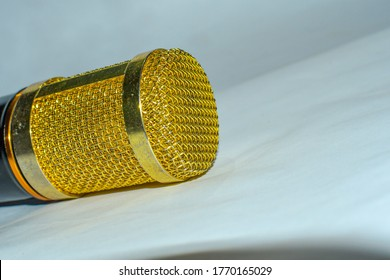 Golden colour microphone close up view on white background.