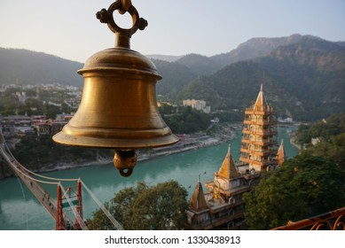 the golden colour temple bell on background of panoramic view of Rishikesh with turquoise waters of river ganga, yellow ashram, red bridge and himalaya hills