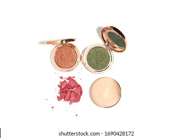 Golden compact eye shadow glitter and shine cosmetic product shot on whitebackground with hi-key harsh shadows