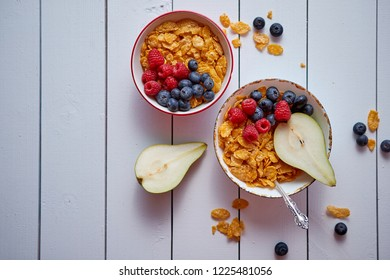 Golden cornflakes with fresh fruits of raspberries, blueberries and pear in two ceramic bowls. Prepared for healthy breakfast. Placed on white wooden table.