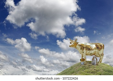 A golden cow on top of a grassy hill against a cloudy blue sky, for the concept of financial cash cow.