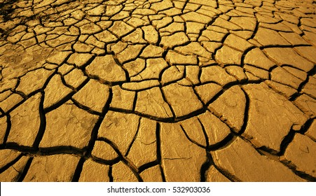Golden crack earth, dry ground surface, gold brown clay soil texture