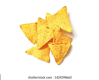 Golden crispy corn chips isolated on white background. Delicious salty mexican triangular nachos. Flat lay food photography