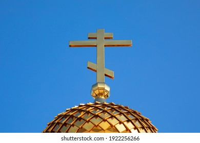 Golden cross and dome of the Orthodox Church against the blue sky. Close-up