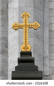 Golden cross on gray stone background. Detail of Temple of Christ the Saviour decoration. Moscow
