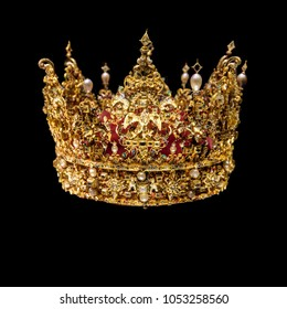 Golden crown with gems isolated on black background.