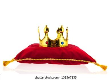 Corona dorada sobre almohada de terciopelo rojo para la coronación