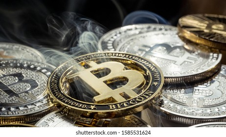 Golden crypto currency Bitcoin coin smoke out laying between other coins