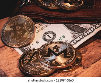 Golden cryptocurrency coins with a leather wallet and one Dollar bill with a wooden surface and dark background.